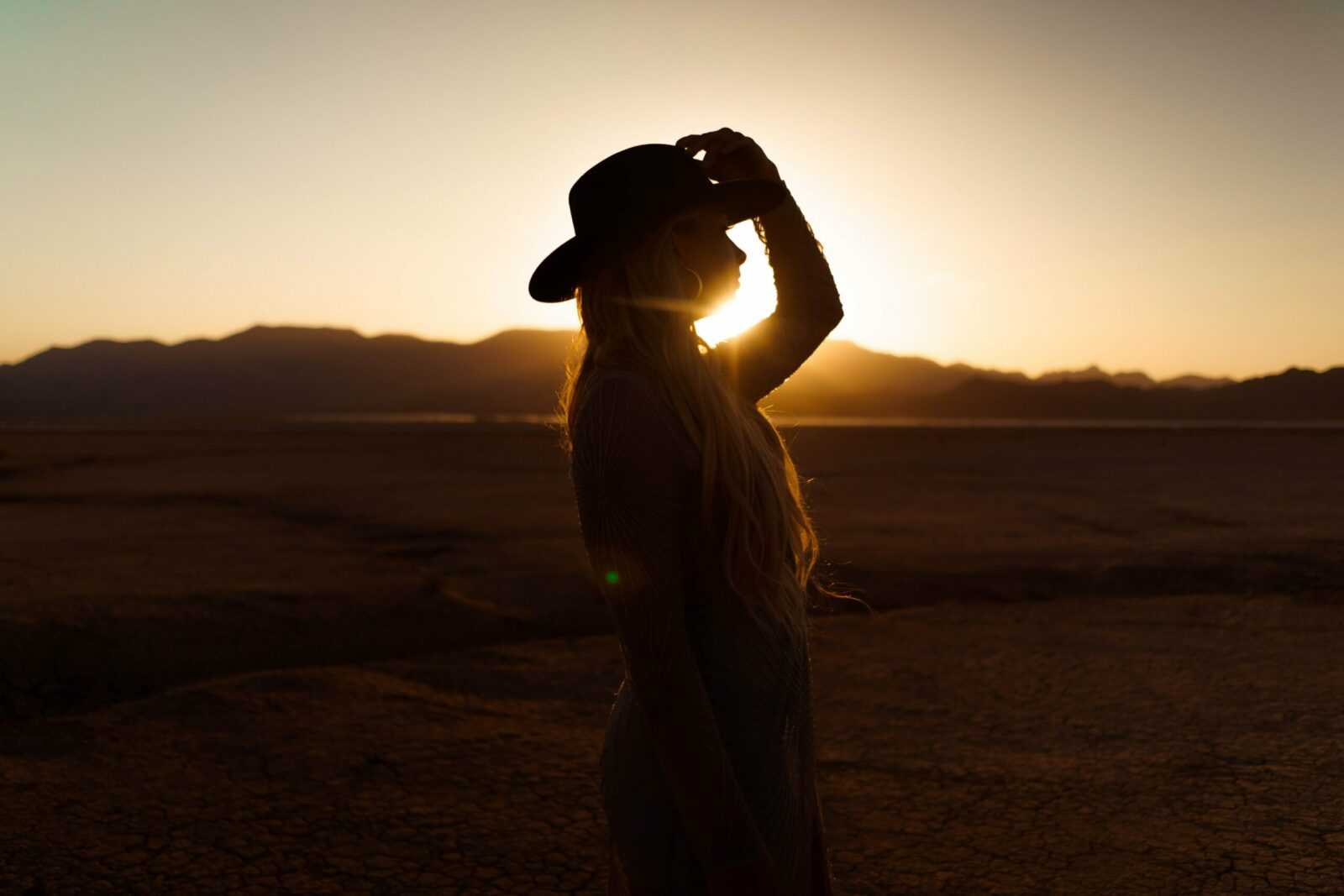 woman in white shirt and black hat standing on beach during sunset