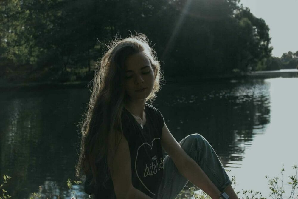 woman in black and white crew neck t-shirt standing near lake during daytime