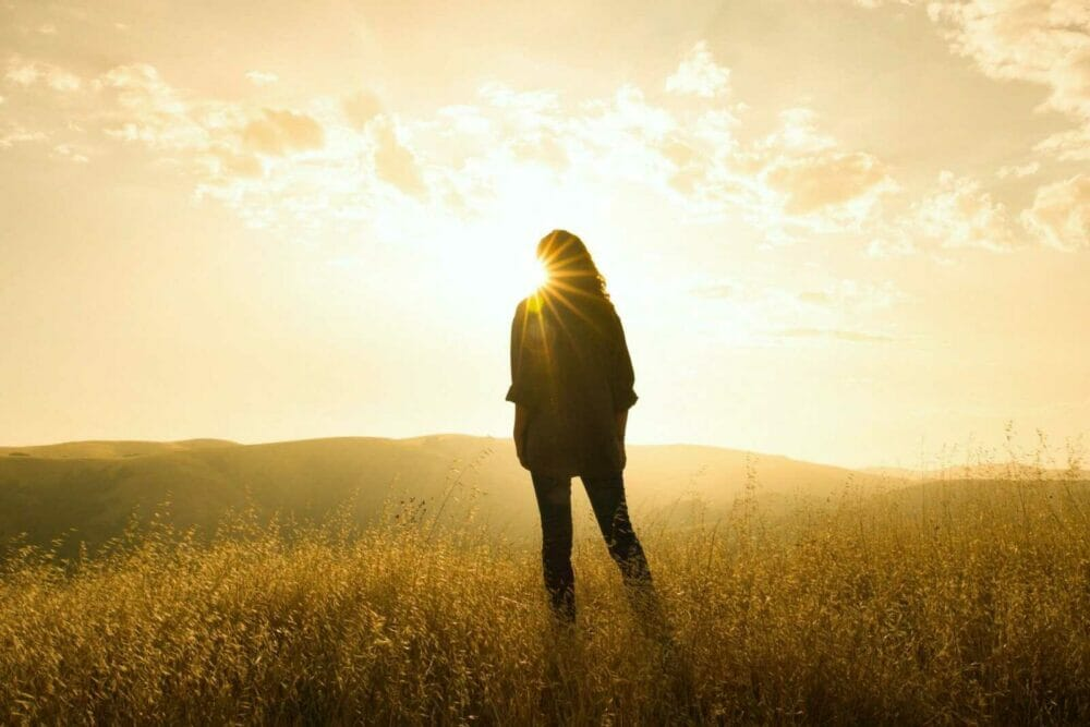 silhouette of person standing on grass while facing sunlight