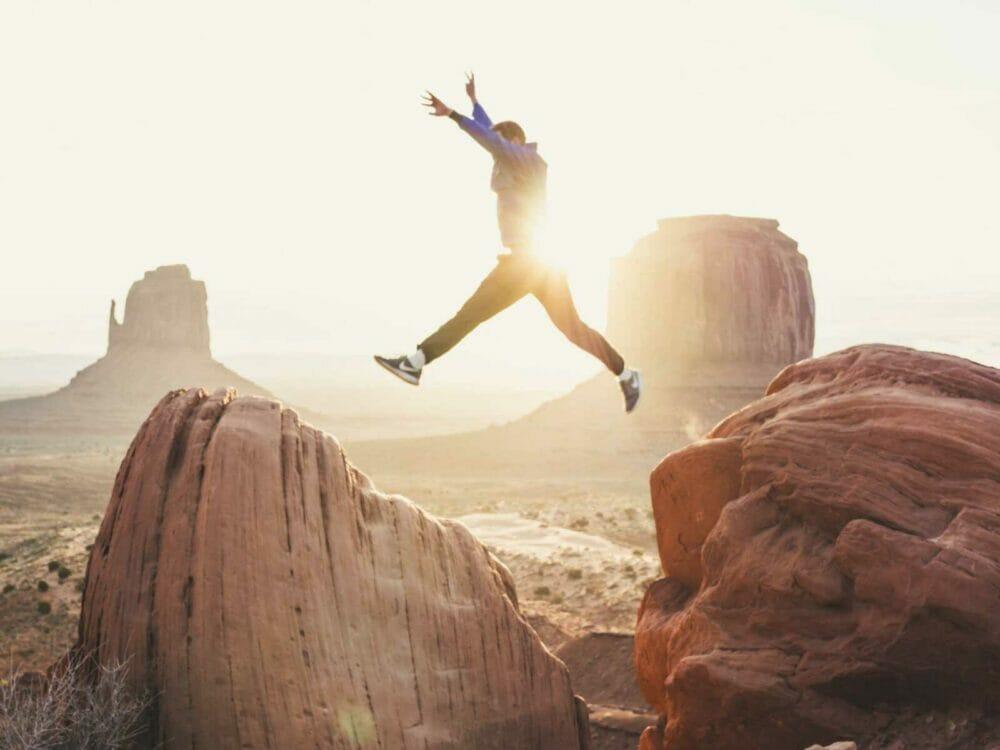 man jumping between two rocks