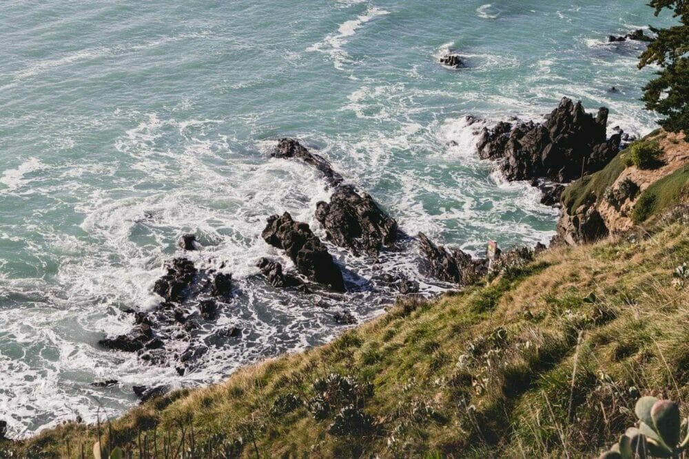 sea waves front of green grass at daytime