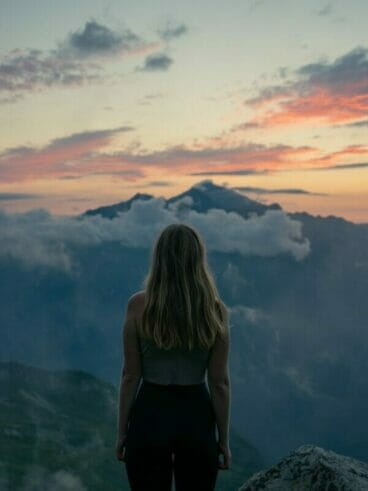 woman in black tank top standing on top of mountain during daytime