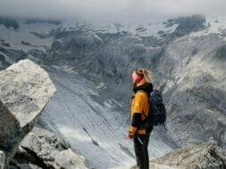 man in orange jacket standing on rocky mountain during daytime