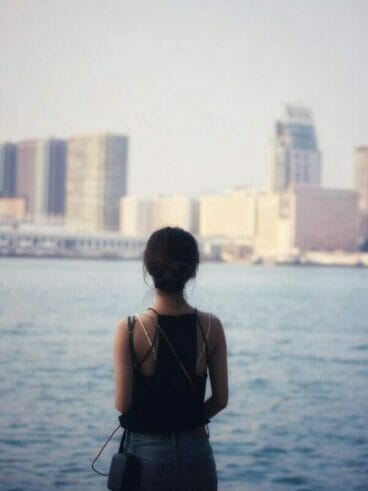 woman in black tank top standing near body of water during daytime