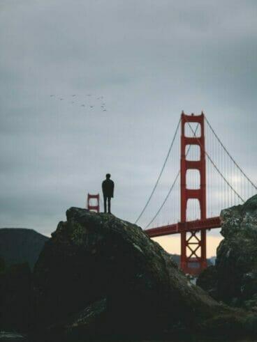 silhouette of man standing on rock near Golden Gate bridge